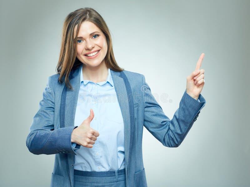 Усмехаясь бизнес-леди указывая на экземпляр размечает и выставки thumb вверх стоковые изображения