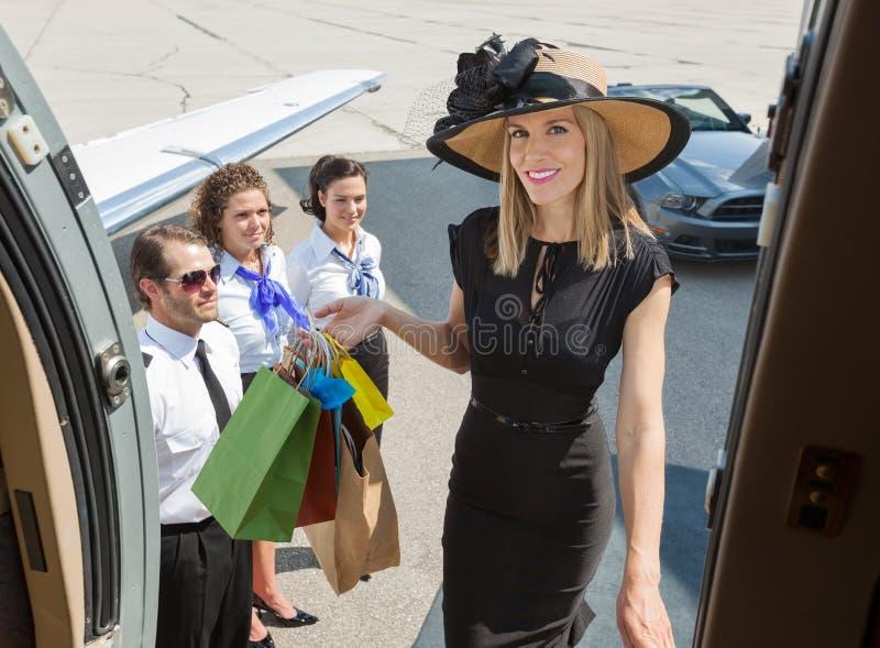 Усмехаясь богатая женщина с восхождением на борт хозяйственных сумок стоковые изображения rf