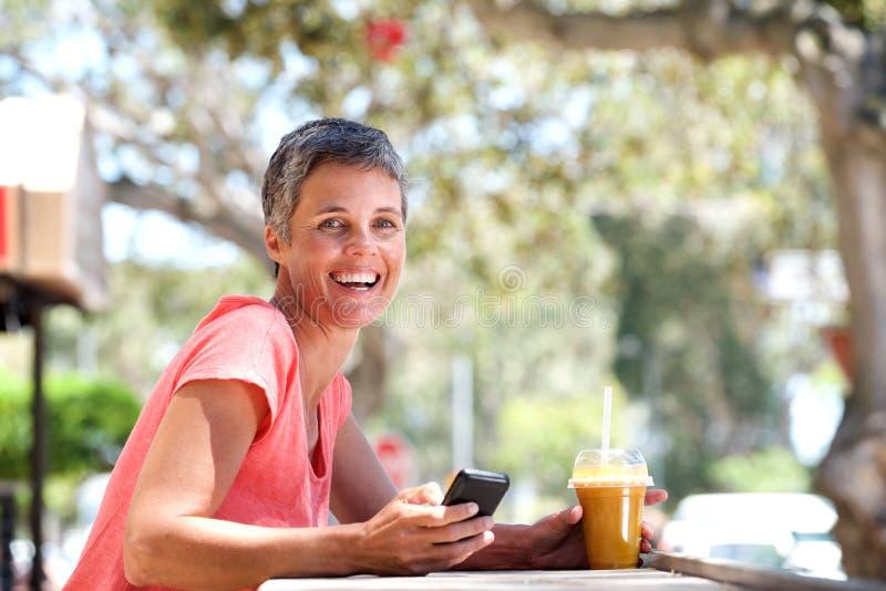 Усмехаясь более старая женщина сидя снаружи с мобильным телефоном и питьем стоковые изображения rf