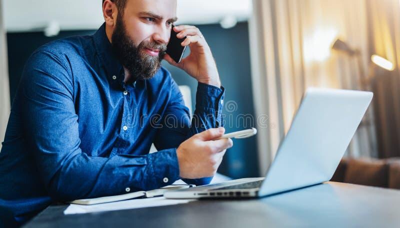 Усмехаясь бородатый бизнесмен сидя на таблице перед компьютером, говорящ на сотовом телефоне, показывая ручку на экране компьтер- стоковое изображение