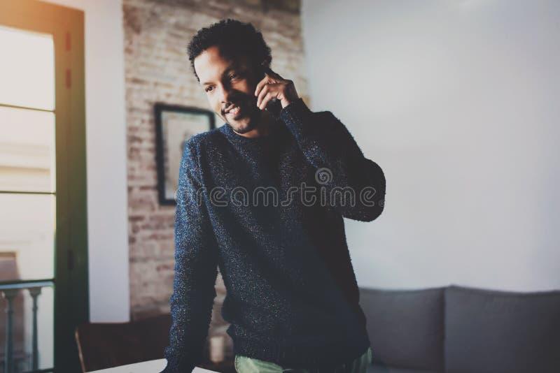 Усмехаясь бородатый африканский человек говоря на smartphone пока стоящ около окна в его современной квартире Концепция  стоковые фотографии rf