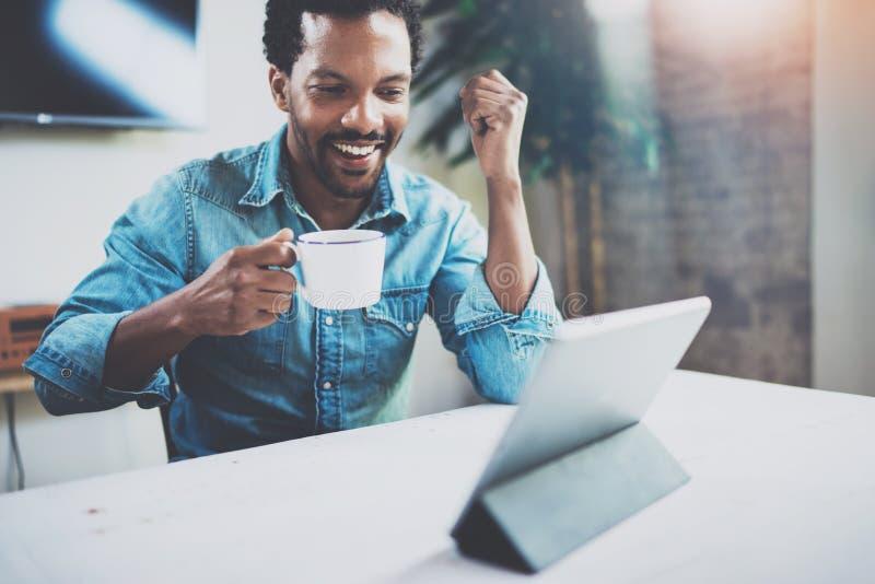 Усмехаясь бородатый африканский человек делая видео- переговор через цифровую таблетку с партнерами пока держащ белую чашку черни стоковые изображения