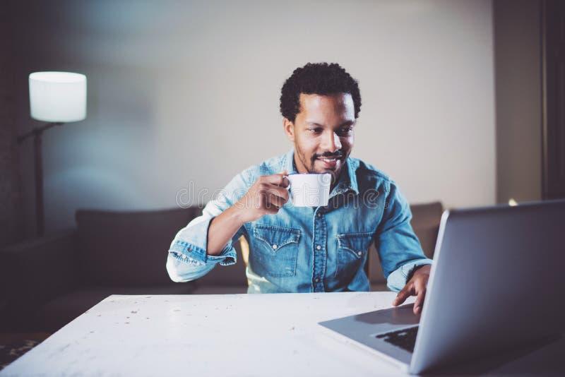 Усмехаясь бородатый африканский человек делая видео- переговор через компьтер-книжку с партнерами пока держащ чай белой чашки чер стоковая фотография
