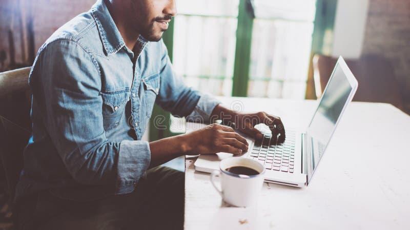 Усмехаясь бородатый африканский человек используя компьтер-книжку дома пока сидящ деревянный стол Гай печатает на клавиатуре тетр стоковое изображение