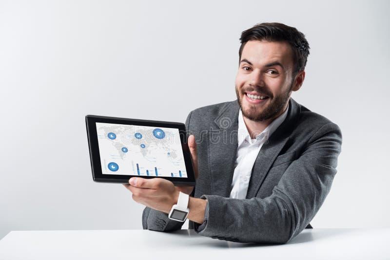 Усмехаясь бородатый человек держа таблетку стоковые фото
