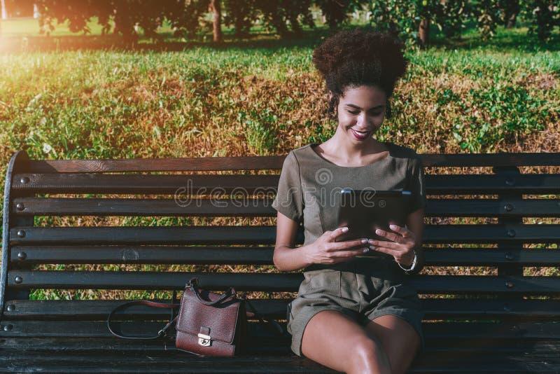 Усмехаясь бразильская женщина с цифровой таблеткой в сквере стоковое изображение