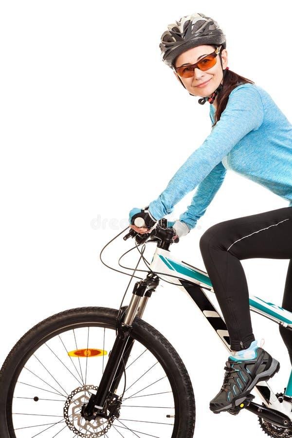Усмехаясь велосипедист взрослой женщины ехать велосипед стоковое фото
