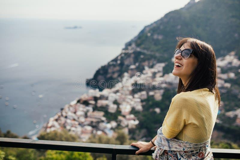 Усмехаясь вид на море молодой женщины enoying в Positano, Италии Каникулы на туристе Амальфи coastHappy в Европе Итальянская крас стоковые изображения rf