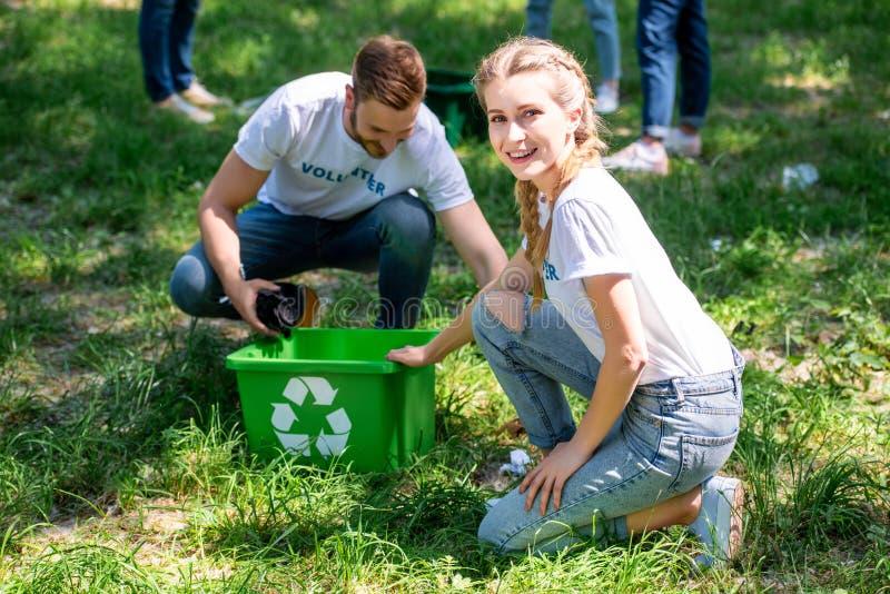 усмехаясь волонтеры очищая лужайку с зеленым цветом стоковое фото rf