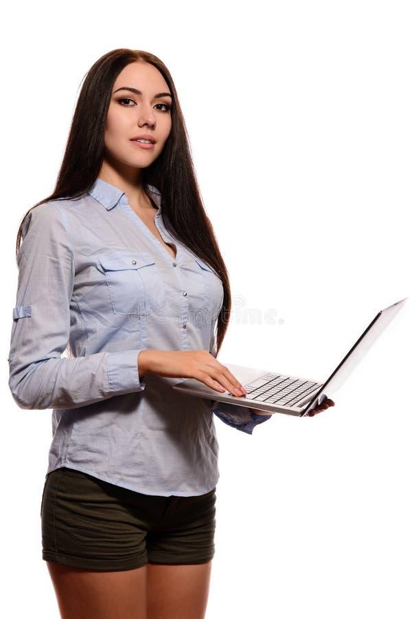 Усмехаясь восточная девушка в рубашке джинсовой ткани была раскрытой компьтер-книжкой стоковое фото rf