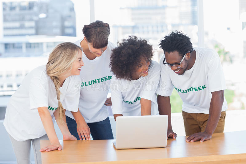 Усмехаясь волонтеры работая совместно на компьтер-книжке стоковая фотография rf