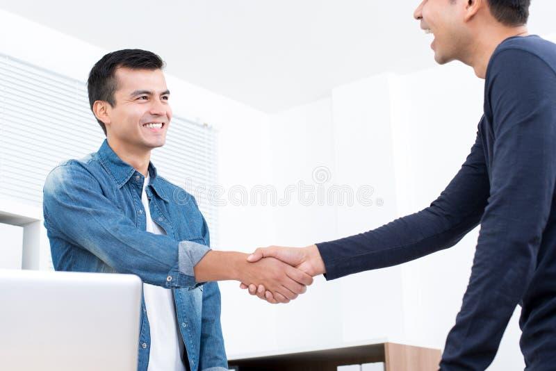 Усмехаясь вскользь бизнесмены делая рукопожатие в офисе стоковое фото