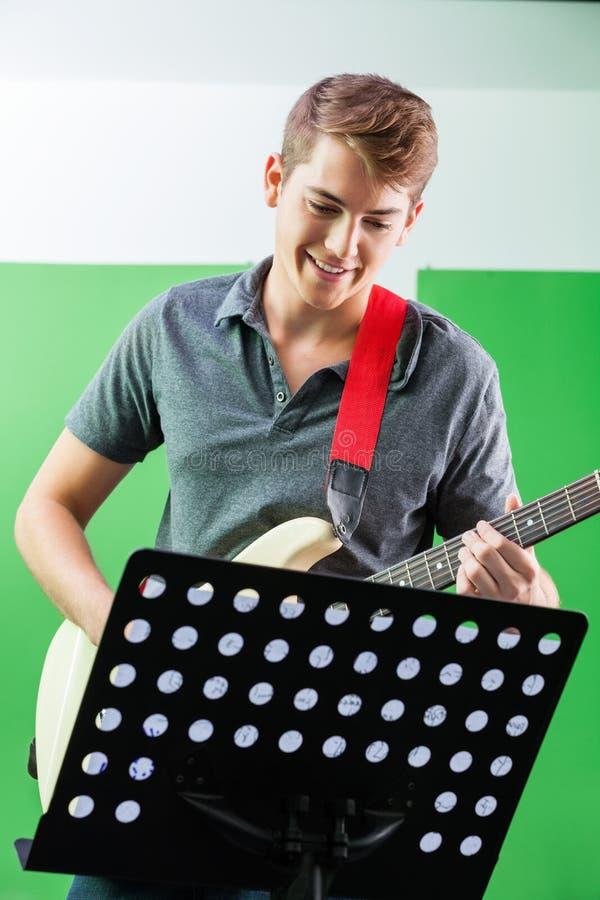 Усмехаясь гитарист выполняя пока смотрящ стоковые изображения