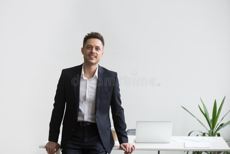 Усмехаясь главный исполнительный директор компании представляя около стола офиса стоковые фотографии rf
