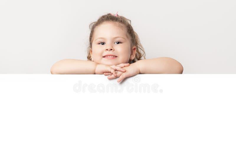 Усмехаясь голубая наблюданная маленькая девочка peeking за белой доской стоковые изображения rf