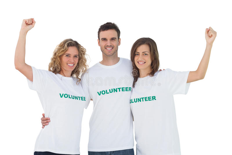 Усмехаясь группа в составе волонтеры поднимая оружия стоковое фото rf