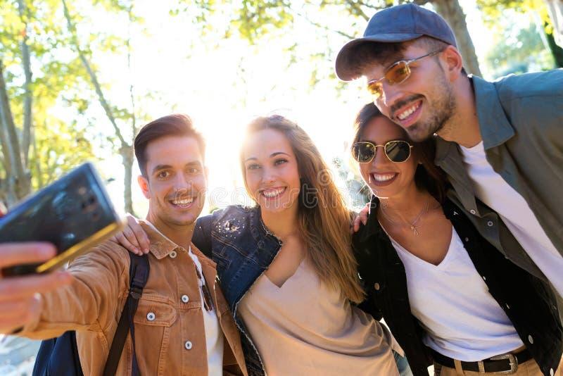 Усмехаясь группа в составе друзья принимая фото с мобильным телефоном внутри ест рынок в улице стоковая фотография rf