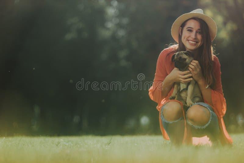 Усмехаясь дама держит мопса в ее руках стоковая фотография