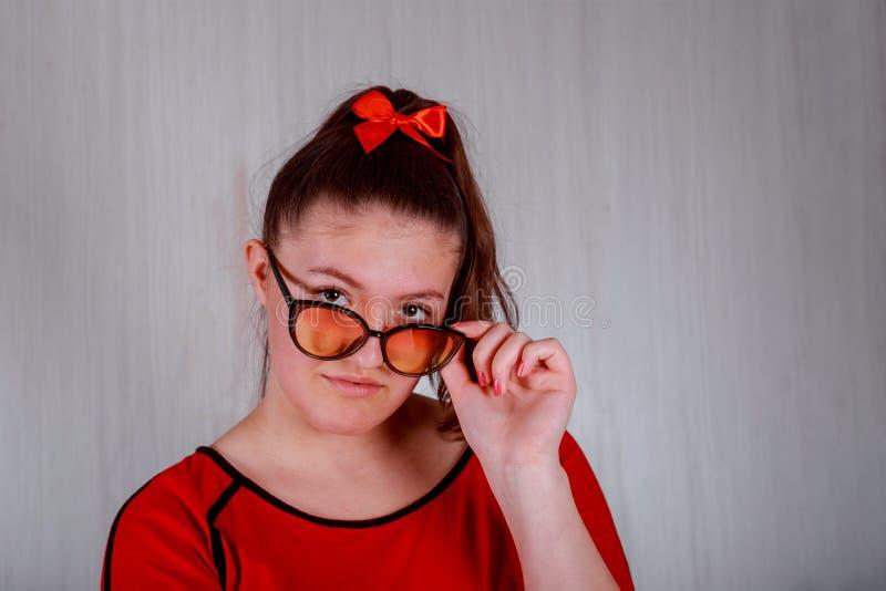 Усмехаясь девушка брюнета милая в eyeglasses представляя смотрящ предпосылку камеры серую белую стоковое изображение rf