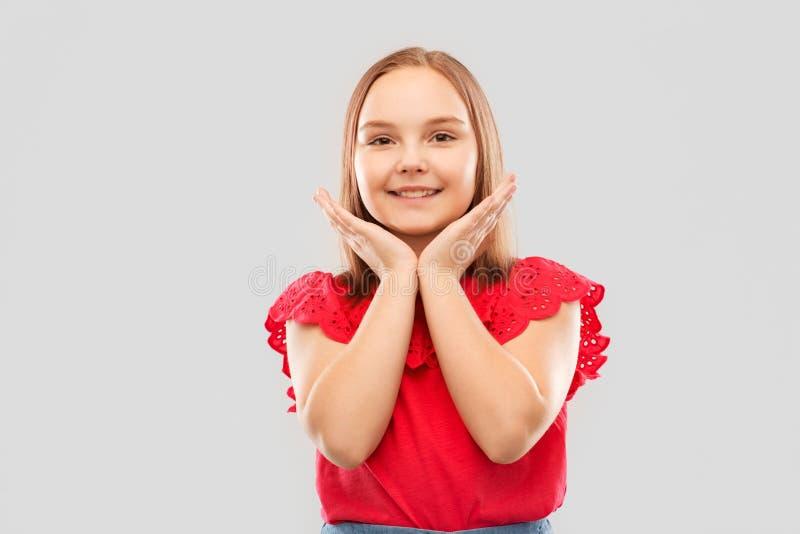 Усмехаясь девушка в красной рубашке представляя над серым цветом стоковые изображения