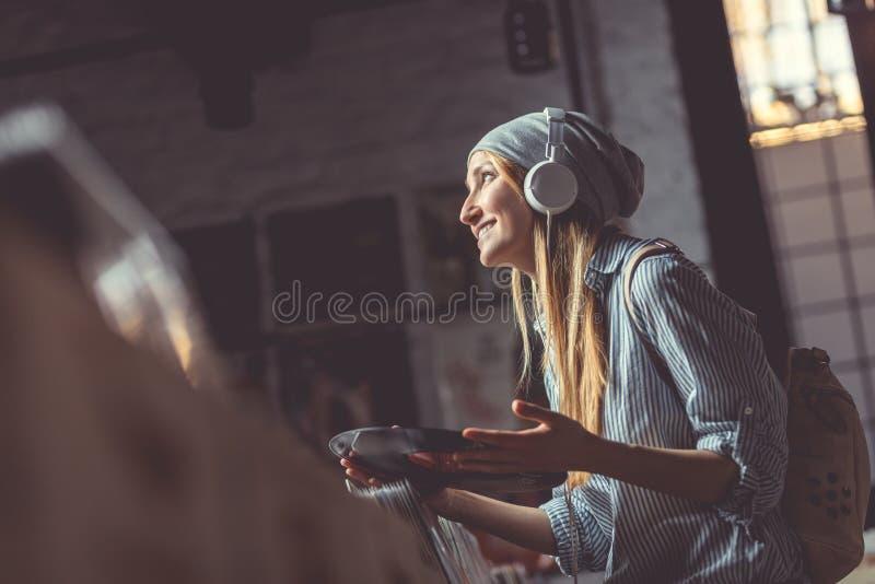Усмехаясь девушка в магазине музыки стоковая фотография rf