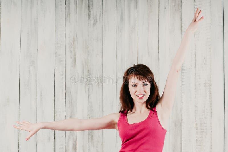 Усмехаясь девушка в розовой верхней части, делая тренировку аэробики стоковые изображения