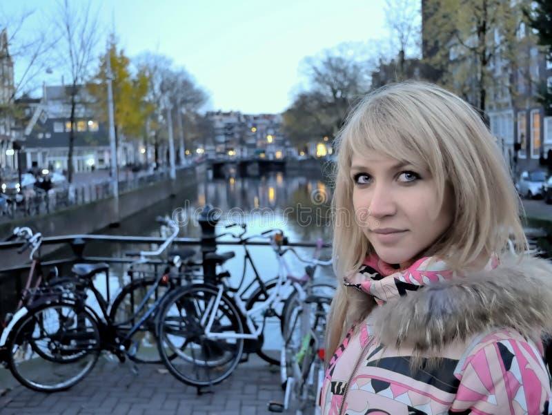 Усмехаясь девушка в розовой куртке около канала Амстердама на голубом вечере часа среди велосипедов стоковое фото rf