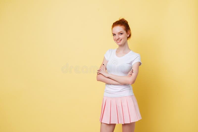 Усмехаясь девушка в футболке и юбке представляя с пересеченными оружиями стоковое изображение rf
