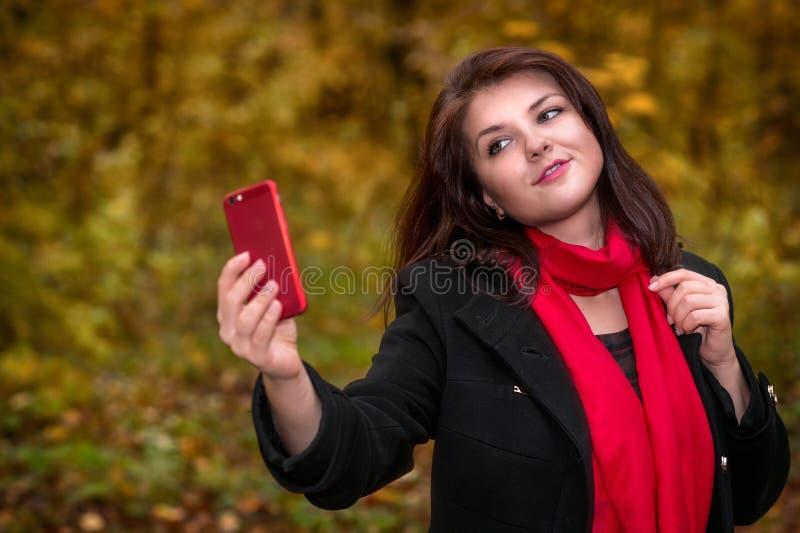 Усмехаясь девушка идет в парк осени и делает selfie стоковые фотографии rf