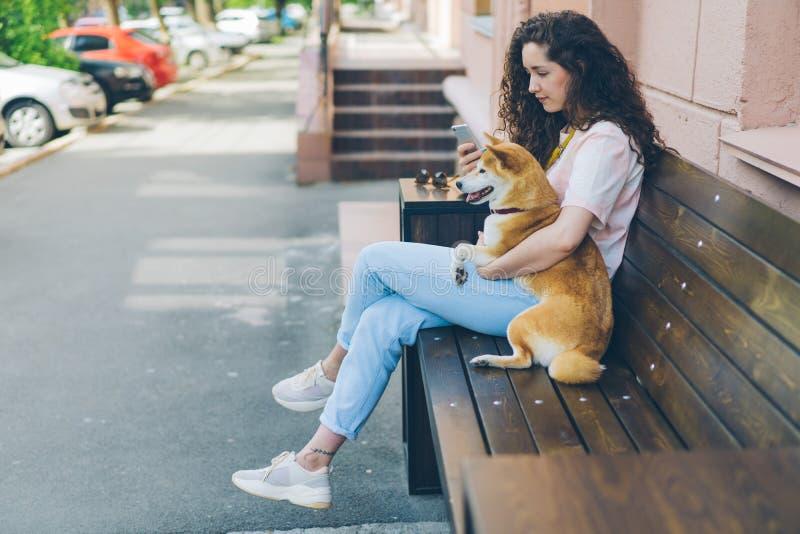 Усмехаясь девушка используя смартфон обнимая прелестную собаку inu shiba outdoors в кафе стоковое фото rf