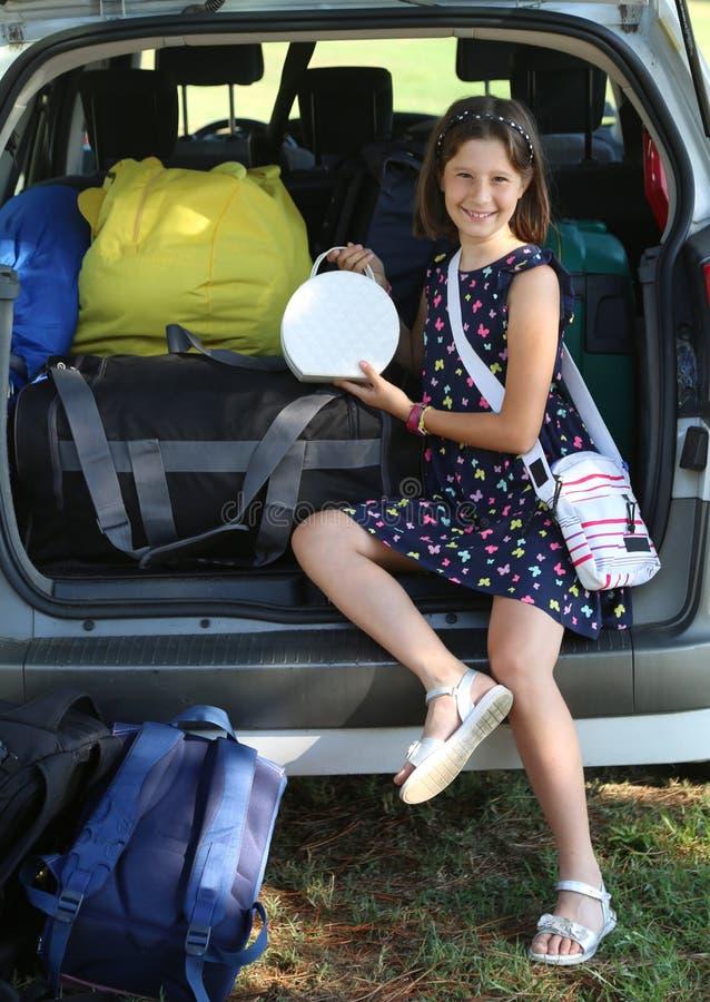 Усмехаясь девушка кладет ее сумку в автомобиль стоковая фотография