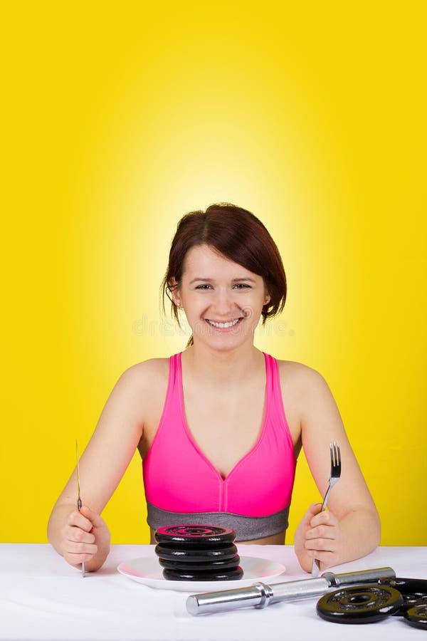 Усмехаясь девушка молодой женщины держа вилку и нож с гантелями в плите стоковые фотографии rf
