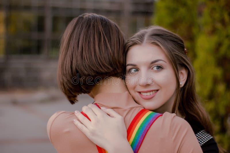 Усмехаясь девушка обнимает его девушку плотно Счастливый красивый студент счастлив встретить друга в парке осени стоковое изображение rf