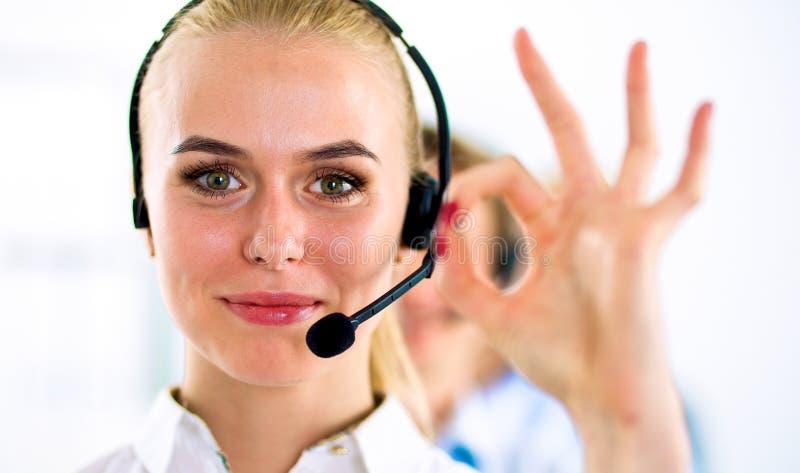 Усмехаясь девушка обслуживания клиента показывая о'кеы, на белой предпосылке стоковые изображения rf