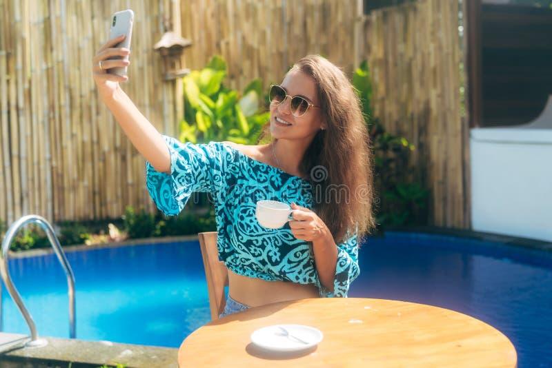 Усмехаясь девушка сидит outdoors на таблице с чашкой чаю или кофе и телефон польз, делают selfie стоковая фотография