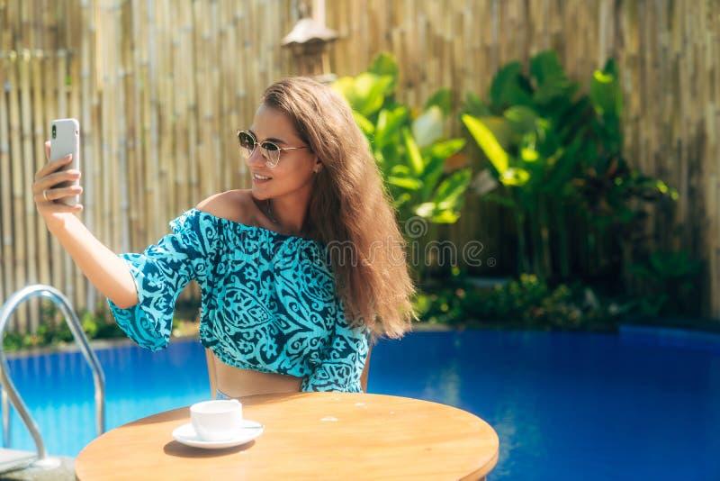Усмехаясь девушка сидит outdoors на таблице с чашкой чаю или кофе и телефон польз, делают selfie стоковые изображения