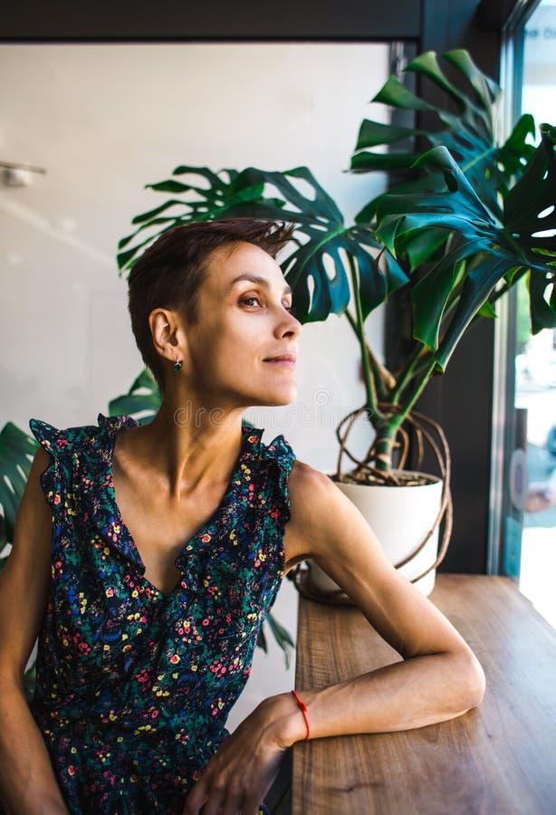 Усмехаясь девушка сидя в кофейне и смотреть вне окно стоковое фото rf
