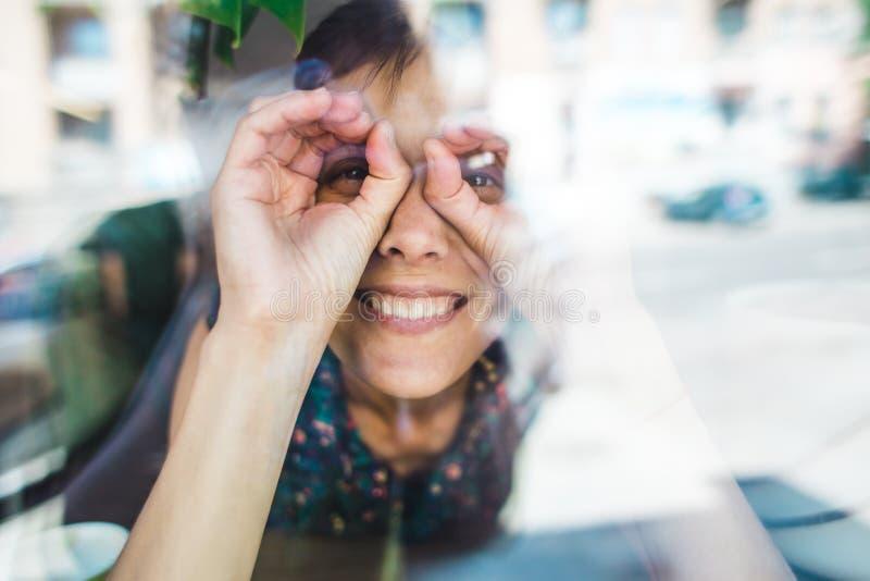 Усмехаясь девушка сидя в кофейне и смотреть вне окно стоковые фотографии rf