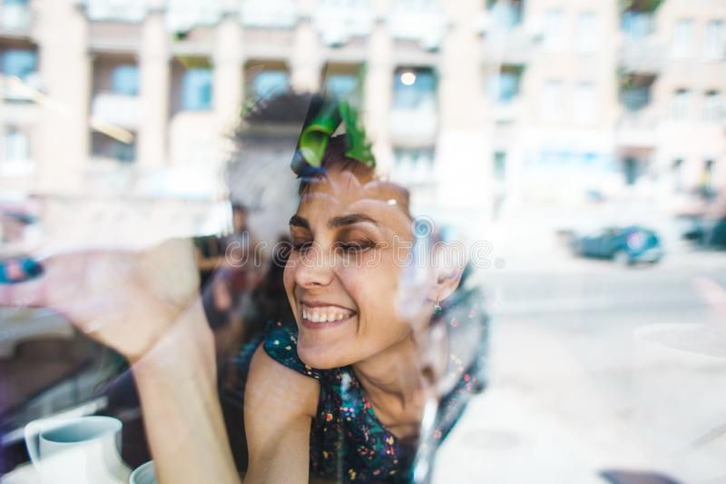 Усмехаясь девушка сидя в кофейне и смотреть вне окно стоковые изображения rf