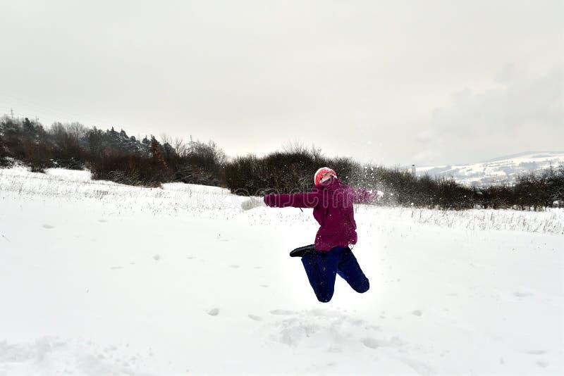 Усмехаясь девушка скачет и падает в снег стоковая фотография rf