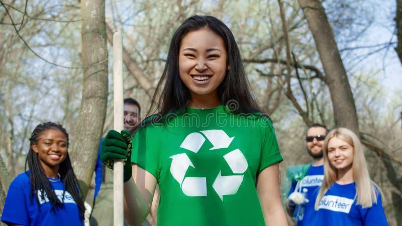 Усмехаясь девушка с группой в составе волонтеры стоковое изображение rf
