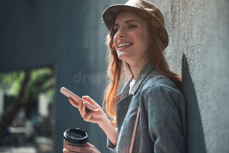 Усмехаясь девушка с чашкой кофе и smartphone стоковое фото rf