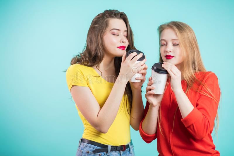 2 усмехаясь девушки студентов выпивая кофе утра, вдыхают ароматность кофе Удовольствие, релаксация, счастье стоковые фото