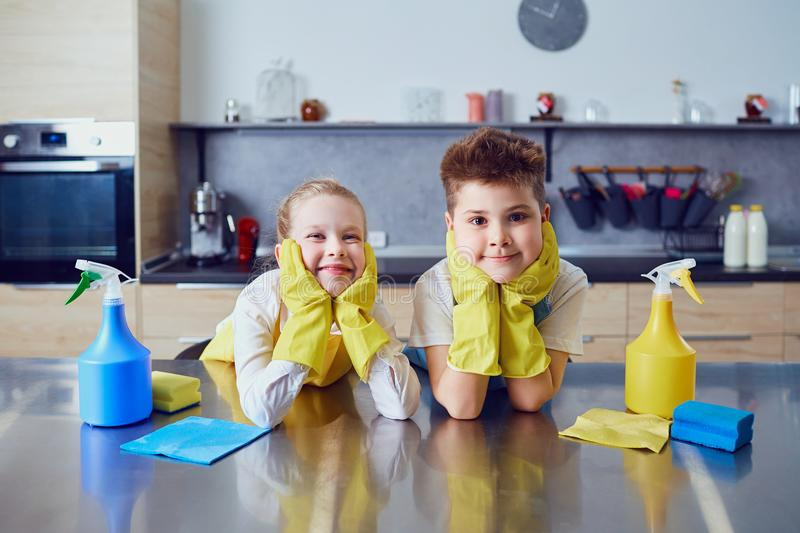 Усмехаясь дети делают чистку в кухне стоковое изображение rf