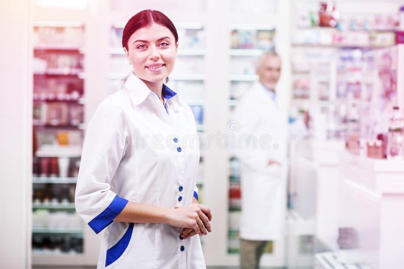 Усмехаясь деятельность формы женщины нося белая как druggist в фармации стоковая фотография rf