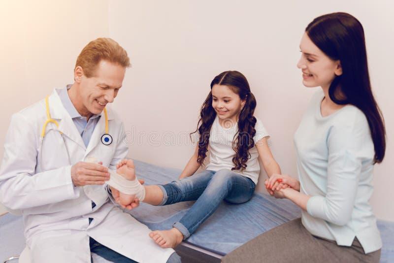 Усмехаясь доктор перевязывая меньшую ногу стоковые фото