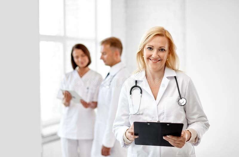 Усмехаясь доктор с доской сзажимом для бумаги и стетоскопом стоковое изображение