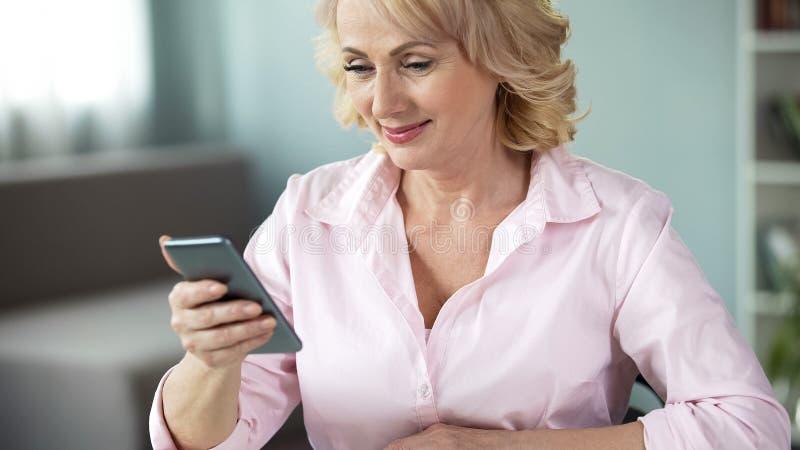 Усмехаясь достигшая возраста дама выглядя онлайн смартфоном фото, социальной связью системы стоковые изображения rf