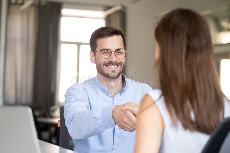 Усмехаясь дружелюбная женщина handshaking бизнесмена на собеседовании для приема на работу, стоковые изображения