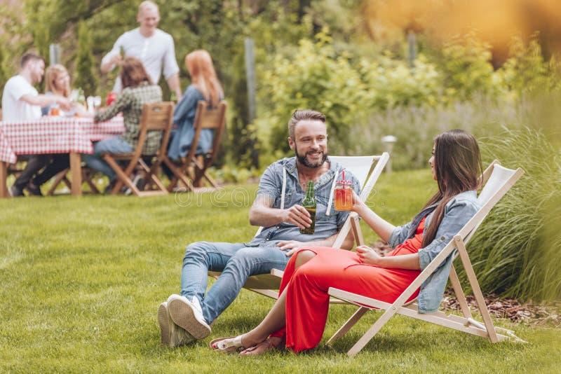 Усмехаясь друзья веселя во время встречи пока ослабляющ на sunbeds в саде стоковое фото